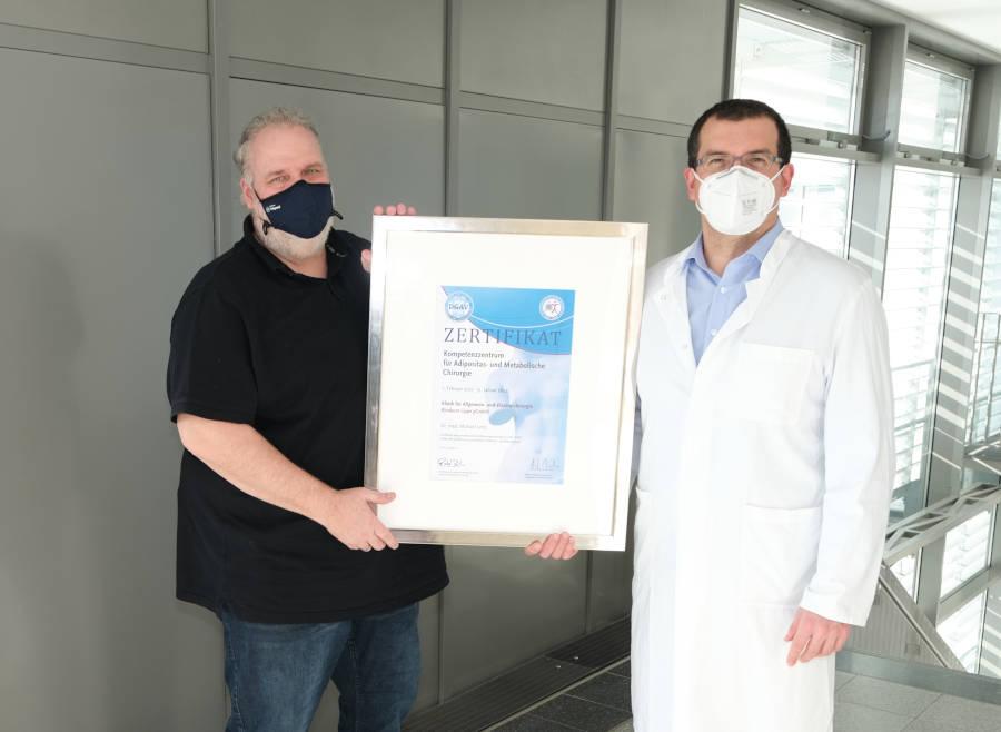 Witterungs- und Coronabedingt war das offizielle Zertifikat länger unterwegs als üblich. Doch nun halten Dr. Michael Leitz und Ralf Sann die DGAV-Zertifizierungsurkunde für das Kompetenzzentrum für Adipositaschirurgie in den Händen. Foto: Klinikum Lippe.