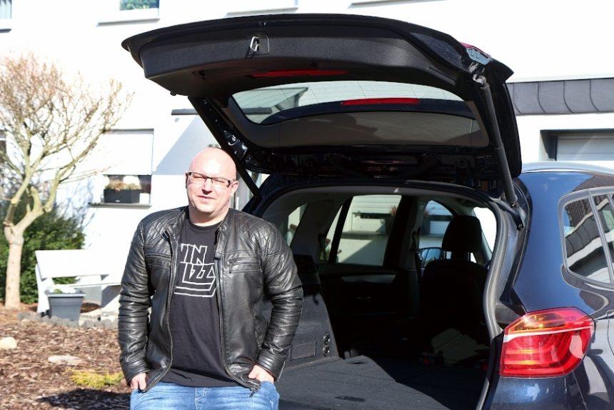 Der Discjockey Dennis Jorczick sitzt am offenen Kofferraum seines Autos. Er hat es im Frühjahr gekauft, um seine Ausstattung besser transportieren zu können. Bisher hat er den Laderaum dafür wegen der Corona-Beschränkungen noch nicht nutzen können. Foto: Thomas Dohna