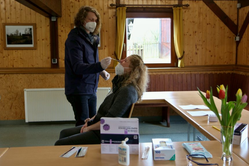 Christian Fabek führt ein Teststäbchen in die Nase von Liselotte Hasselhoff ein. Das Wattebäuschen an der Spitze muss die Schleimhäute im Nasen-Rachenraum erreichen. Dort gibt es die meisten Viren, wenn es sie dort gibt. Foto: Thomas Dohna