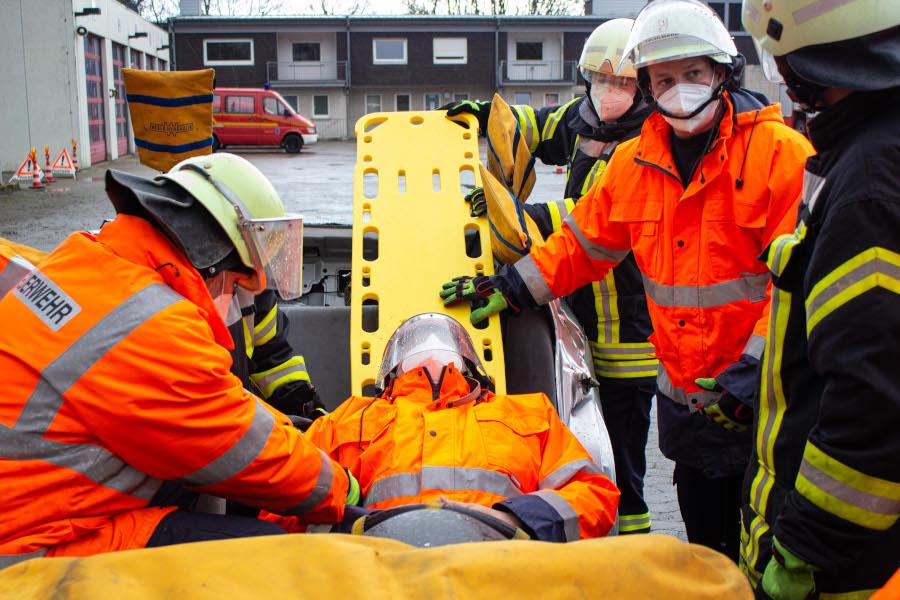 """Angehende Truppmänner lernen, wie ein Verletzter möglichst schonend aus einem Auto gerettet werden kann. Das Dach haben sie schon abschnitten. Jetz schieben sie eine spezielle Trage unter den """"Verletzten"""". Foto: Leon Stock / Feuerwehr Bad Salzuflen"""