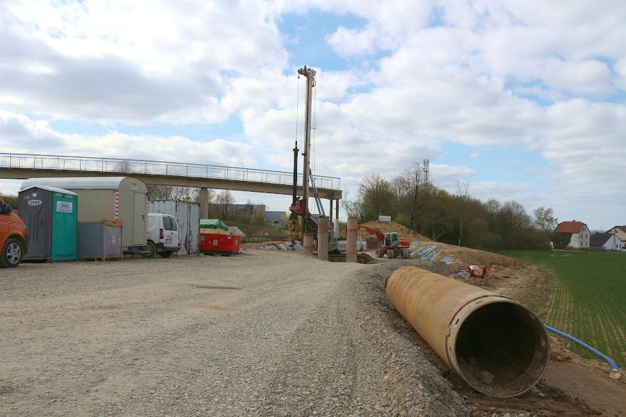 """An der Nordseite der Brücke """"Am Bollholz"""" bohrt eine Maschine Löcher für Betonpfähle. Sie fangen die geplante Stützwand ab. Das Rohr rechts wird in den Boden getrieben. Dahinein kommt ein Baustahlgitter, das mit Beton ausgegossen wird. Foto: Thomas Dohna"""