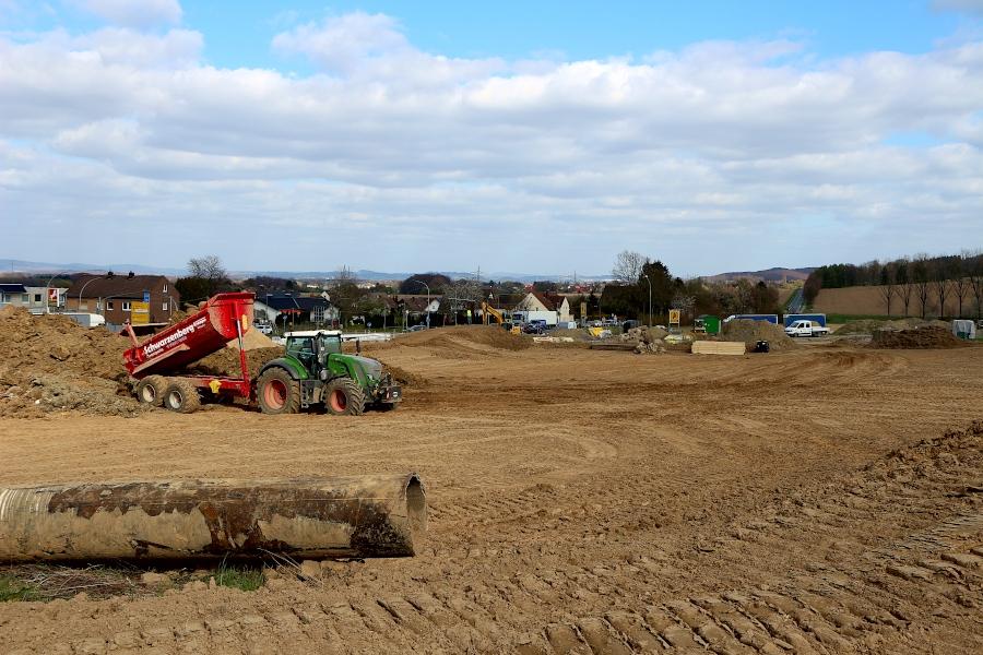 Vor ein paar Tagen wucherte hier noch Gestrüpp. Jetzt ist die Fläche freigeschoben. Ein Traktorfahrer lädt Boden aus Baugruben ab. Foto: Thomas Dohna