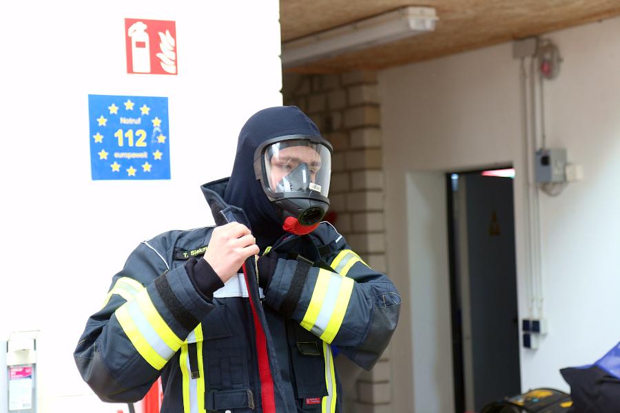 Über die Atemschutzmaske gehört eine Brandschutzhaube, die sich der Teilnehmer des Lehrgangs unter der Einsatzjacke zurechtschiebt. Foto: Thomas Dohna