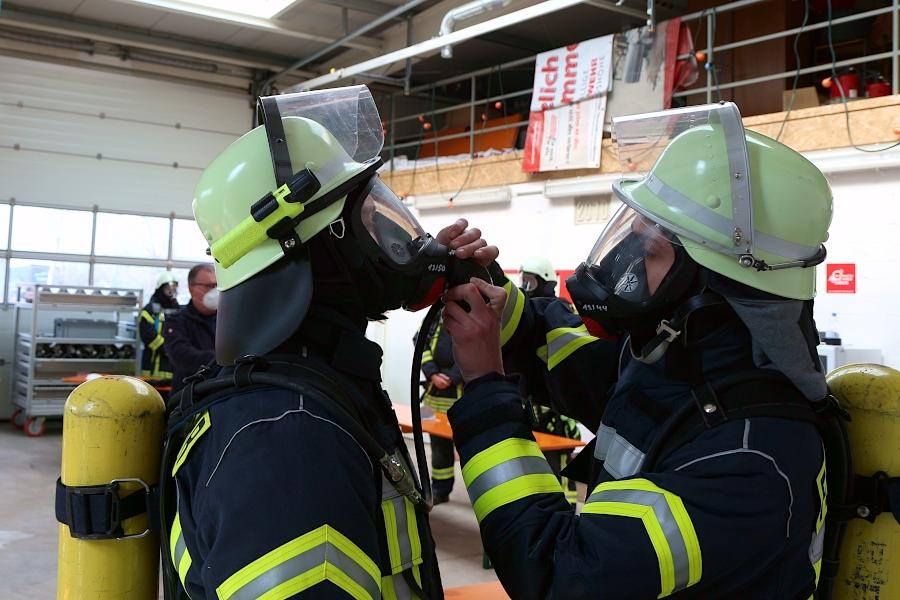 Die beiden Wehrleute helfen sich gegenseitig beim Anschluss des Atemautomaten. Der muss an der Maske angeschraubt werden. Foto: Thomas Dohna