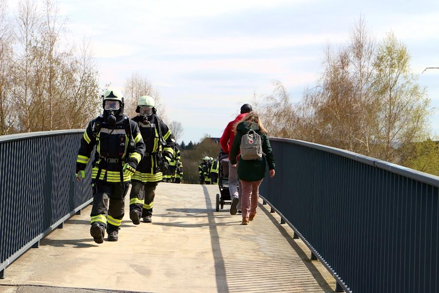 Auf der Brücke über die Teutoburger Straße begegnen die Marschierenden Passanten. Die hören bei jedem Atemzug der Wehrleute das Zischen der Atemschutzgeräte. Foto: Thomas Dohna
