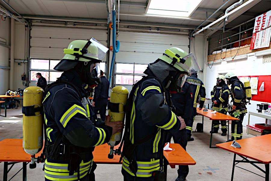 Ein Feuerwehrmann hilft seinem Trupppartner, das Atemschutzgerät aufzusetzen. Foto: Thomas Dohna
