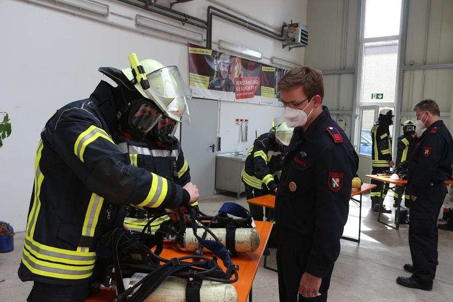 Unterbrandmeister Max Schewe schaut zu, wie die beiden angehenden Atemschutzgeräteträger ihre Geräte vorbereiten. Foto: Thomas Dohna