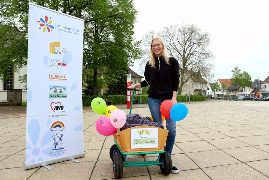 Astrid Bondzio vom Jugendzentrum Leos steht mit einem Bollerwagen auf dem Marktplatz in Leopoldshöhe. Aus dem Bollerwagen heraus verteilt sie Basteltüten für zuhause. Foto: Thomas Dohna