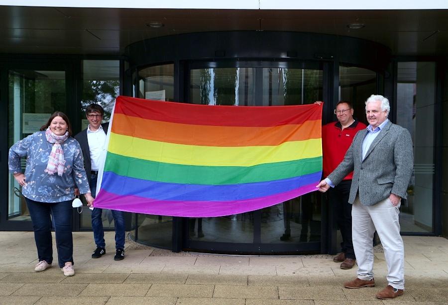 Christiane Frevert (Grüne), Bürgermeister Martin Hoffmann sowie die Fraktionsvorsitzenden Thomas Jahn (SPD) und Hermann Graf von der Schulenburg (FDP) halten die Regenbogenfahne. Sie wollen so ein Zeichen gegen den Hass gegen sexuell nicht hetero orientierte Menschen setzen. Foto: Thomas Dohna