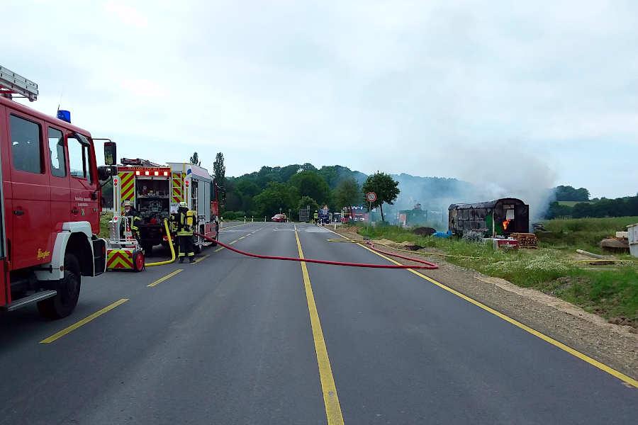 Flammen schlagen aus dem Bauwagen an der Tunnelstraße. Zwei Fahrzeuge der Freiwilligen Feuerwehr Leopoldshöhe haben sich aufgestellt. Im Hintergrund rücken gerade die Oerlinghauser Löschfahrzeuge an. Foto: Freiwillige Feuerwehr Leopoldshöhe / Christoph Keßler