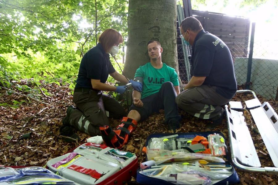 Marcel Freitag hat sich im Wald eine Fußverletzung zugezogen. Die Rettungshelferin Christiane Maßmann misst den Blutdruck. Rettungshelfer Mike Messing beobachtet ihn. Hinter Messing liegt die Schaufeltrage, mit der der Patient aus dem Wald getragen werden könnte. Foto: Thomas Dohna