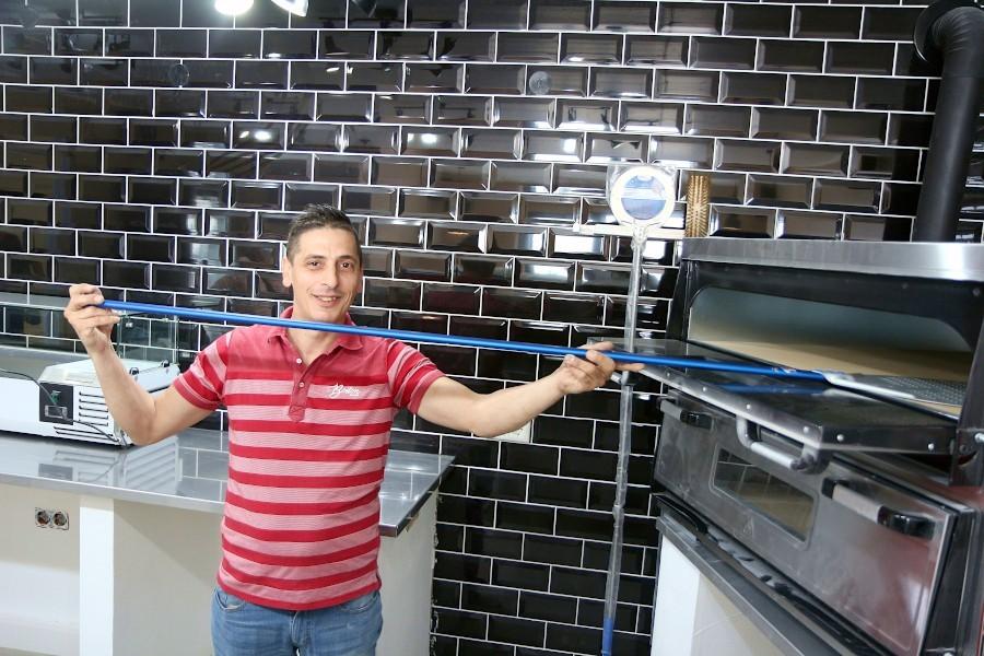 Daniele Ventura steht an seinem neuen Pizzaofen. Noch muss viel gerichtet und saubergemacht werden. Am Samstag will er seine ersten Gäste in der neuen Pizzeria an der Hauptstraße empfangen. Foto: Thomas Dohna