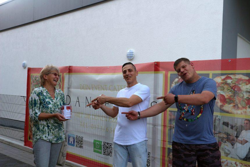 Doris Eversmeier hat die mit 1.000 Euro gefüllte Spendendose aus den Händen Daniele Venturas (Mitte) entgegengenommen. Dessen Nachbar und Freund Julian Stoll half bei der Eröffnung von Danieles Pizzeria am Samstag. Foto: Thomas Dohna