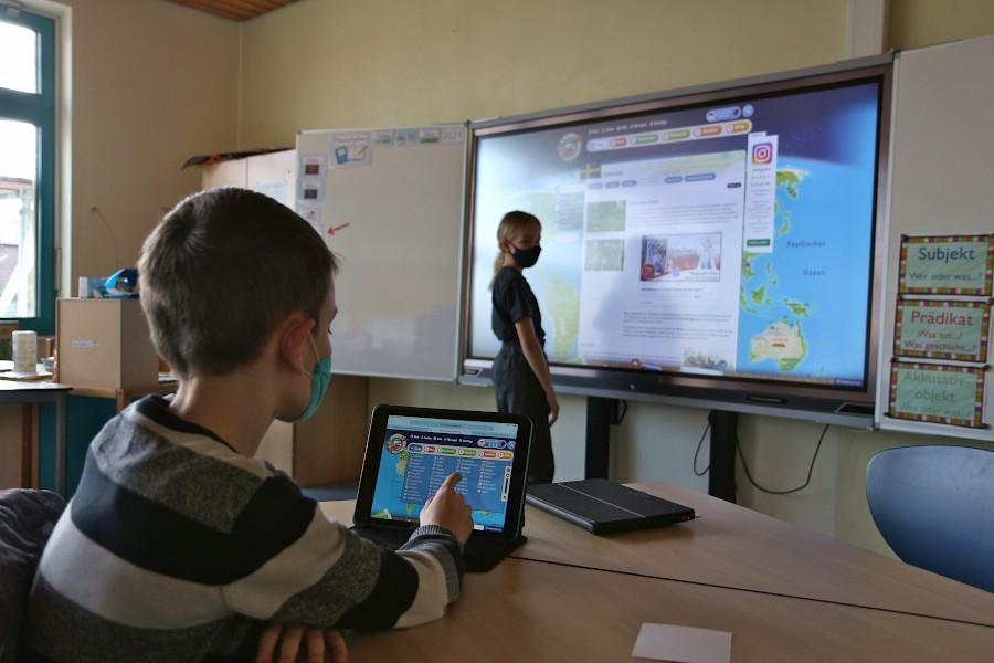Eine Schülerin der Grundschule Asemissen steht am Smartboard in ihrem Klassenraum. Sie hat gerade von einer Lernplattform einen Beitrag zum Sachkundeunterricht aufgerufen. Der Schüler im Vordergrund sucht auf seinem Tablet einen anderen Beitrag. Foto: Thomas Dohna
