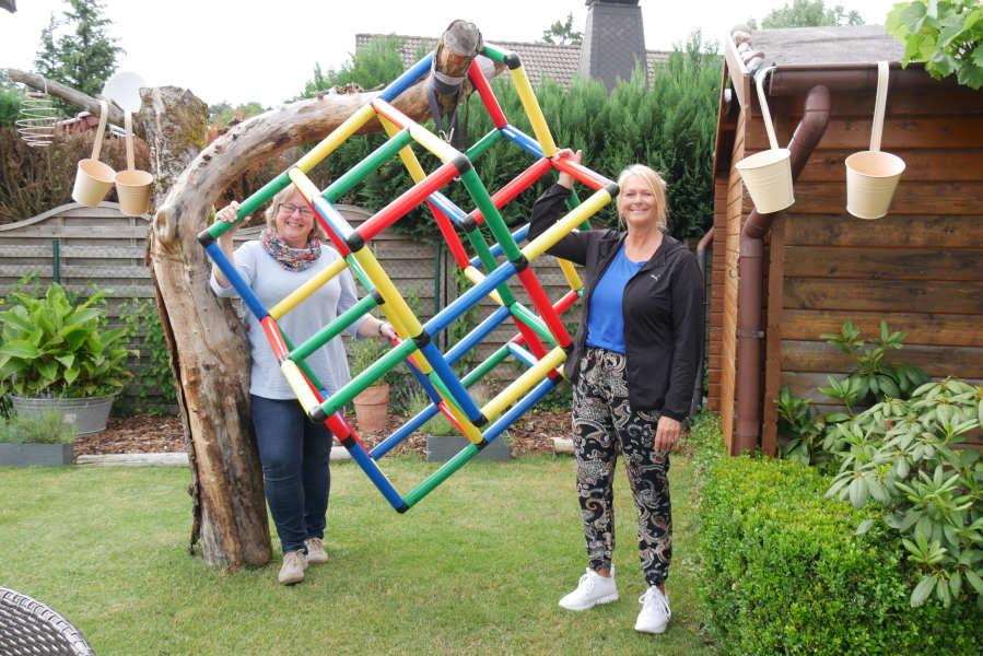Fürs Foto am Baum: bevor die Kinder kommen, wird das Klettergerüst natürlich wieder auf den Rasen gestellt. Dagmar Freitag (rechts) und Antje Höper packen es gemeinsam an.