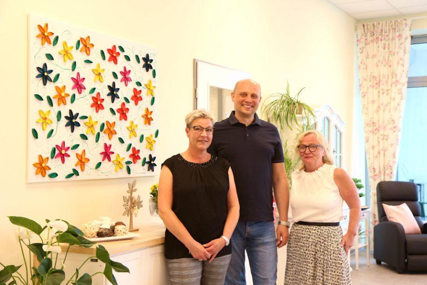 Yvonne Hoppe (links), Alexander Wittlif und Gabriele Frühling zeigen die neuen Räume der Tagespflege Asemissen oberhalb des Kaufhauses Asemissen. Das Bild haben Gäste der Tagespflege erarbeitet. Foto: Thomas Dohna