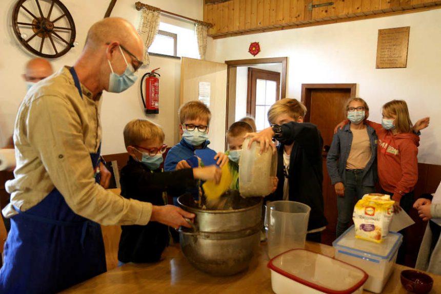 Birk, Florian, Andreas und Aske (von links nach rechts) geben den vorbereiteten Sauerteig in die große Metallschüssel. Guido Letmathe hilft den Kindern. Im Hintergrund warten Anna (links) und Svea auf ihren Einsatz. Foto: Edeltraud Dombert