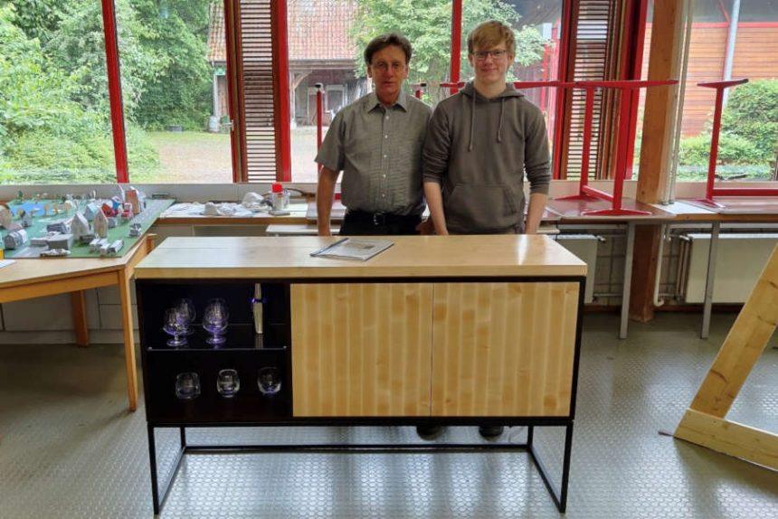 Paul Vollmer (rechts) steht mit seinem Ausbilder Horst Kesting an seinem Gesellenstück, einem Sideboard mit Hausbarfunktion. Foto: Gemeinde Leopoldshöhe