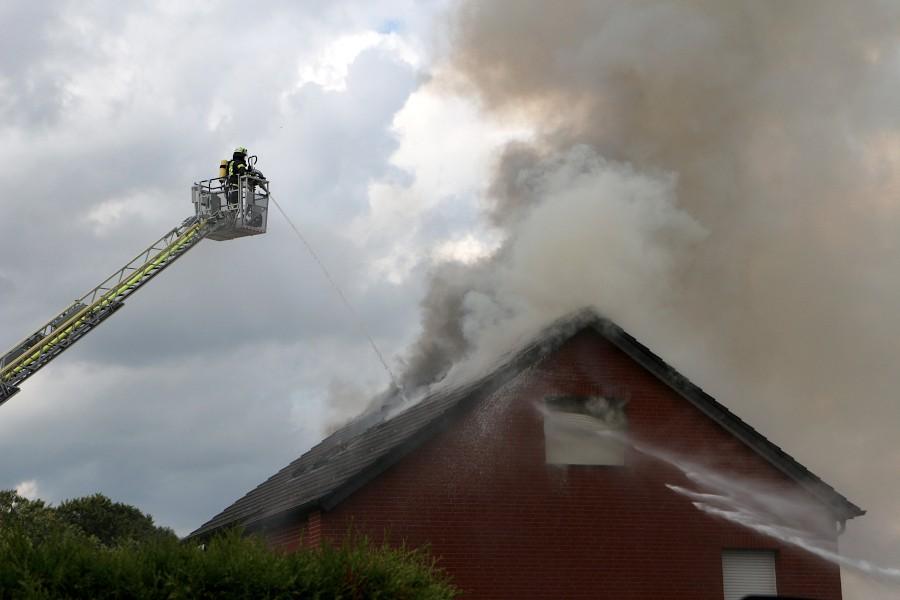 Von der Drehleiter und rechts vom Boden aus gibt die Feuerwehr Wasser auf das Dach. Foto: Edeltraud Dombert