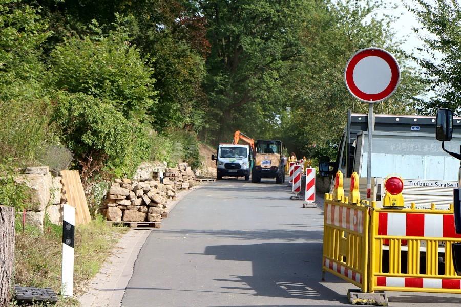 Die Bauarbeiten für die Trockenmauer an der Dorfstraße in Greste ist der Grund für die Sperrung der Straße. Ihre Steine sind auf Paletten gestapelt. Foto: Thomas Dohna