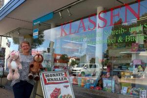 Irina Klassen zeigt die Monatsangebote für September 2021. In ihrem Laden Klassentreff an der Herforder Straße am Leopoldshöher Marktplatz gibt es alles für die Schule, Schreibwaren, Bücher und Spielzeug. Foto: Thomas Dohna