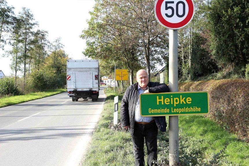 Andreas Brinkmann steht an der Ortshinweistafel für Heipke an der Schackenburger Straße. Gerade ist einer der vielen Lkw durchgefahren, die diese Straße täglich benutzen. Archivfoto: Thomas Dohna