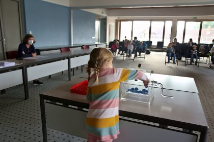 Ein Mädchen aus der Kindertagesstätte Schuckenbaum zieht einen Chip aus der Lostrommel und damit eines der Planungsbüros, die an dem Städtebaulichen Wettbewerb Brunsheide teilnehmen dürfen. Foto: Thomas Dohna