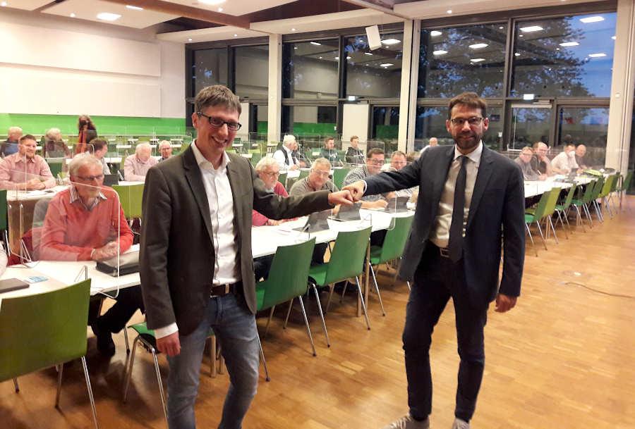 Bürgermeister Martin Hoffmann (links) verabschiedet den bisherigen Kämmerer Leopoldshöhes Uwe Aust. Die Mitglieder des Gemeinderates schauen zu. Foto: Thomas Dohna